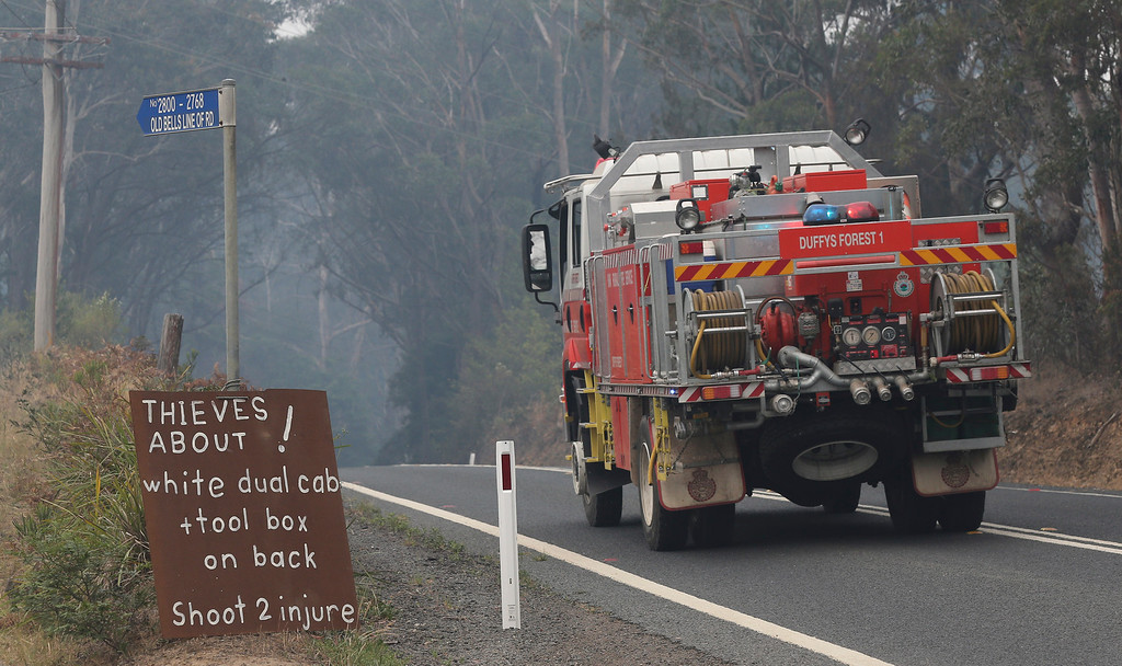 """. A firetruck drives past a roadside sign that says \""""Thieves about!, white dual cab + toolbox on the back, Shoot 2 injure\""""  outside Bilpin,  75 kilometers (47 miles) west of Sydney in Australia, Tuesday, Oct. 22, 2013. Authorities have warned that hotter weather and increased winds are expected and are preparing for the conditions to worsen. (AP Photo/Rob Griffith)"""
