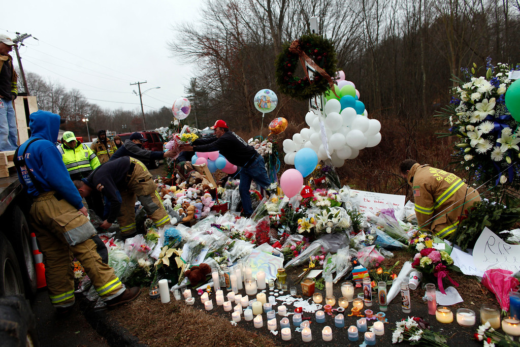 . Firefighters and other volunteers reorganize a memorial for shooting victims near Sandy Hook Elementary School before erecting a shelter over it, Sunday, Dec. 16, 2012 in Newtown, Conn.  A gunman walked into Sandy Hook Elementary School in Newtown Friday and opened fire, killing 26 people, including 20 children. (AP Photo/Jason DeCrow)