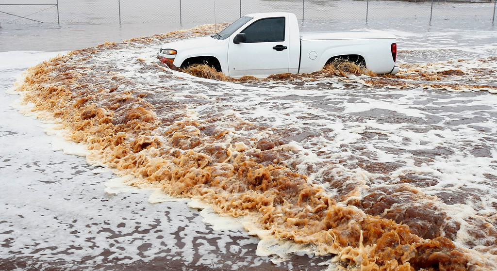 . A truck creates a wake as its driver tries to navigate a severely flooded street as heavy rains pour down Monday, Sept. 8, 2014, in Phoenix. Storms that flooded several Phoenix-area freeways and numerous local streets during the Monday morning commute set an all-time record for rainfall in Phoenix in a single day. (AP Photo/Ross D. Franklin)