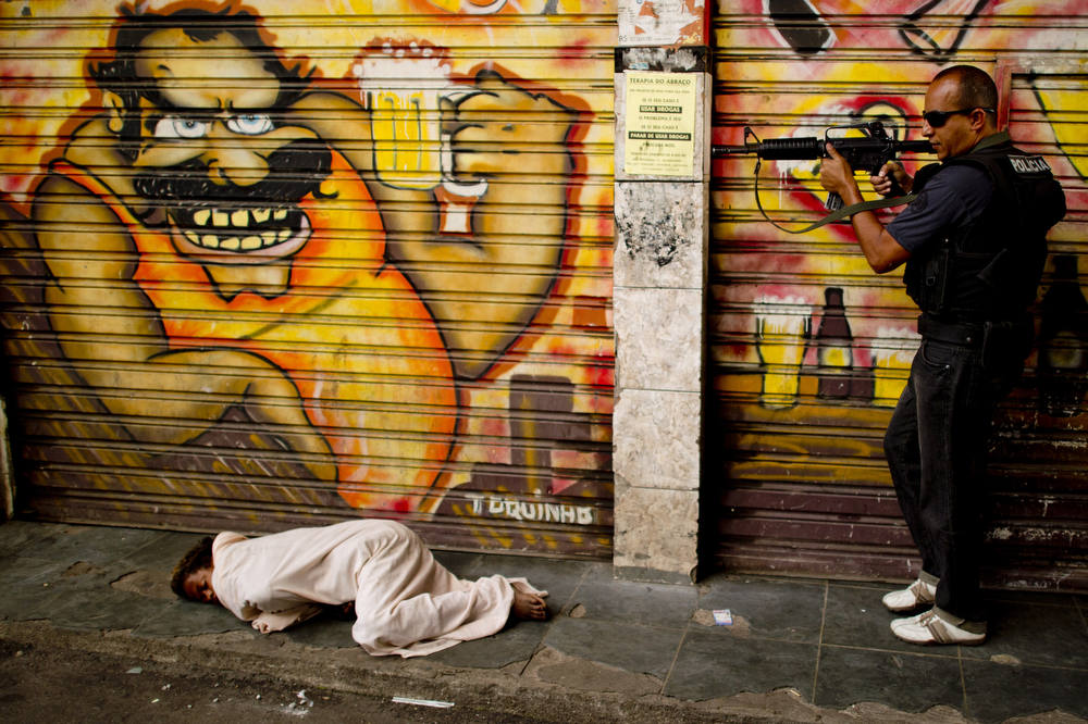Description of . A policeman secures the area before proceeding to pick up a child crack addict sleeping on the sidewalk at the entrance of the Jacare shantytown during an operation to clean the streets of crack addicts, in Rio de Janeiro, Brazil on September 12, 2012. AFP PHOTO/Christophe  SIMON/AFP/Getty Images