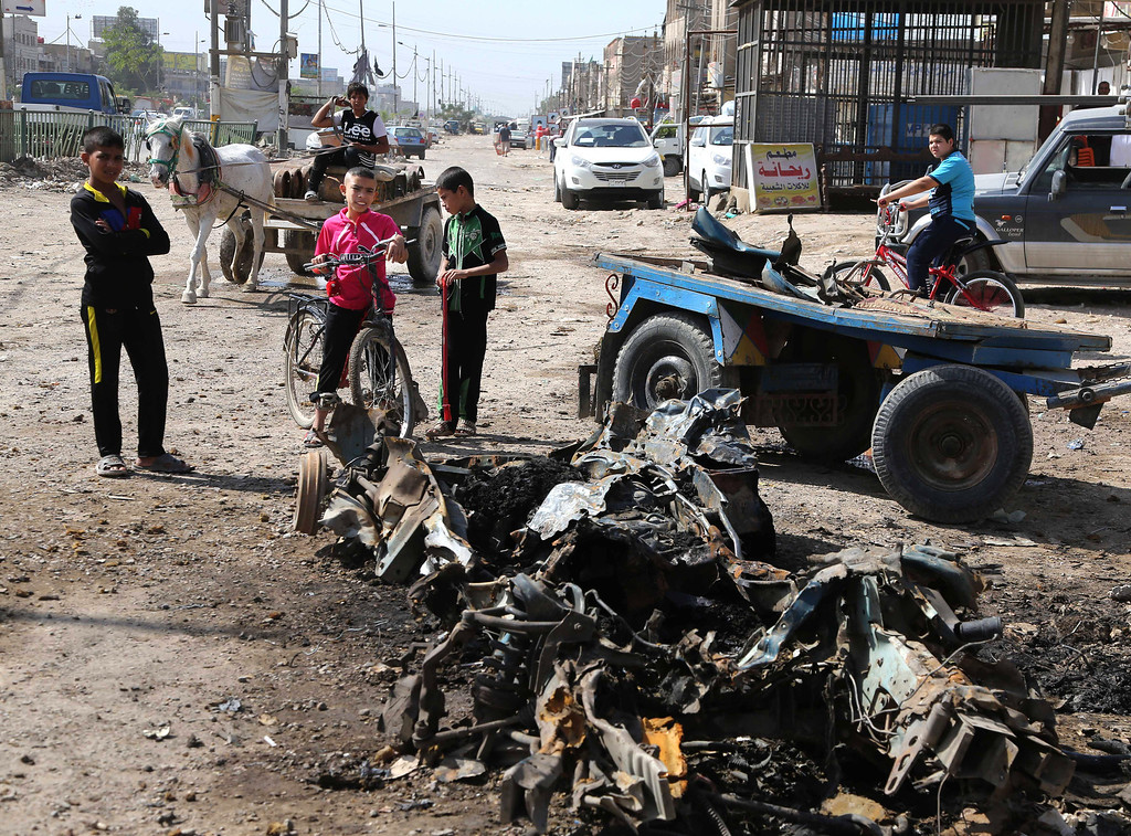 . Civilians inspect a damaged vehicle in the aftermath car bomb attack on Monday in Baghdad northeastern district of Shaab, Iraq, Tuesday, May 13, 2014.  (AP Photo/Karim Kadim)