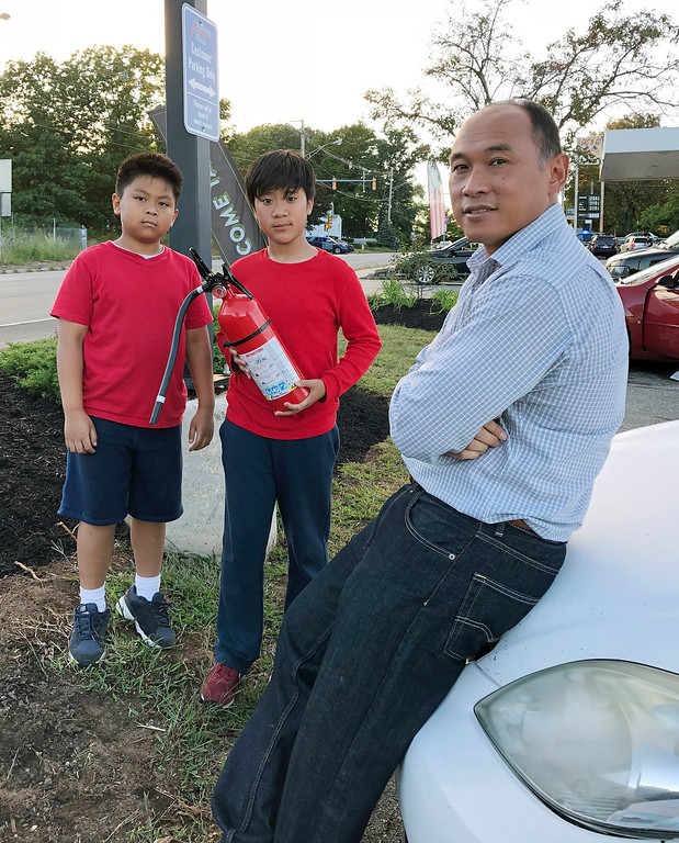 . Ra Nam, right, with his sons Evan, left, and Tristan, center, wait in a parking lot outside their Colonial Heights neighborhood which was evacuated Thursday, Sept. 13, 2018, in Lawrence, Mass., due to fires and explosions triggered by a problem with a gas line that feeds homes in several communities north of Boston. (AP Photo/Phil Marcelo)