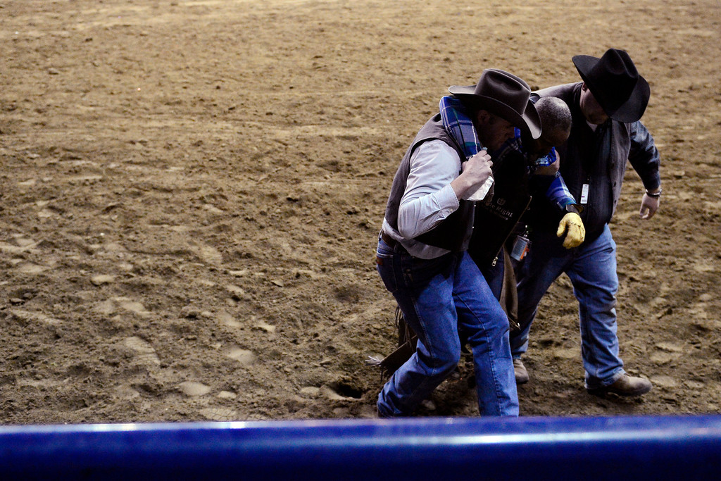 . DENVER, CO. - JANUARY 21: Jimmy Patterson is helped off the arena floor after being knocked out by his bull at the National Western Stock Show Martin Luther King Heritage Rodeo January 21, 2013 (Photo By AAron Ontiveroz / The Denver Post)