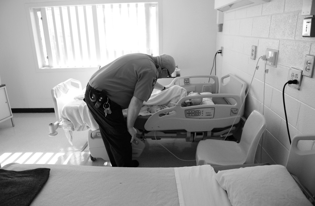 . CANYON CITY, CO. - NOVEMBER 08: At the end of his shift, sergeant James Winston checks on Robert Bryan before heading home, November 08, 2012. The guard, who has worked in the prison system for nine years and is growing old himself, spends extra time with the aging inmates in the infirmary. (Photo By RJ Sangosti/The Denver Post)
