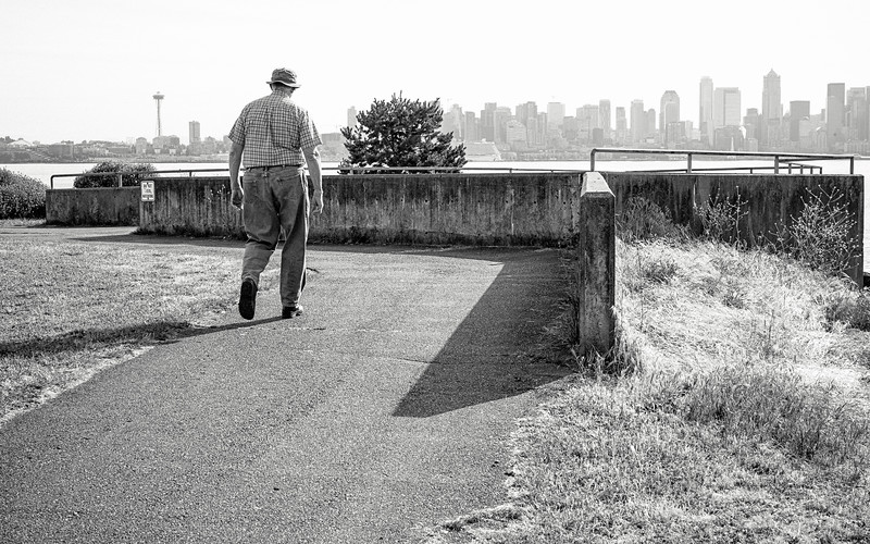 An older man enjoys a walk along the path Alki Trail in West Seattle.