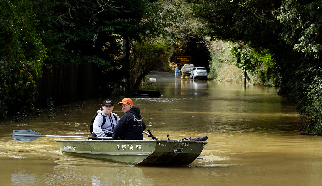 . Residents traverse a flooded street by rowboat, Friday, Feb. 10, 2017, in Guerneville, Calif. The Russian River rose above its flood stage again on Friday due to excessive rain in the area causing minor flooding. (AP Photo/Ben Margot)