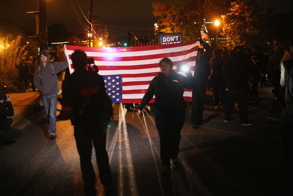 . FERGUSON, MO - OCTOBER 10:  Demonstrators protest outside the Ferguson police department on October 10, 2014 in Ferguson, Missouri. Ferguson has been plagued with protests which have sometimes turned violent since the death of 18-year-old Michael Brown who was shot and killed by Darren Wilson, a Ferguson police officer, on August 9.  (Photo by Scott Olson/Getty Images)