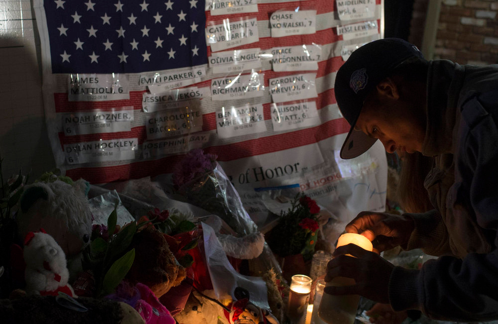 . A man lights a candle in front of a flag with the names of victims who died in the December 14 shootings at Sandy Hook Elementary School in Sandy Hook village in Newtown, Connecticut, December 17, 2012. The two funerals on Monday ushered in what will be a week of memorial services and burials for the 20 children and six adults massacred at Sandy Hook Elementary School in Newtown, Connecticut. REUTERS/Adrees Latif
