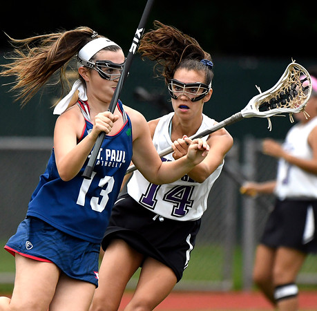 5/31/2018 Mike Orazzi | Staff St. Paul Catholic High School's Olivia Stump (13) and North Branford High School's Ali Barrett (14) during the girls Class S Quarterfinals lacrosse at North Branford High School Thursday evening.