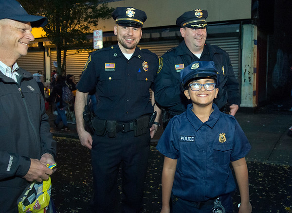 10/31/19 Wesley Bunnell | StaffrrPolice Capt. Adam Rembisz and Chief Christopher Chute stand with trick or treater Luis Fontanez, age 10, during the New Britain Down District Halloween Safe Zone 2019.