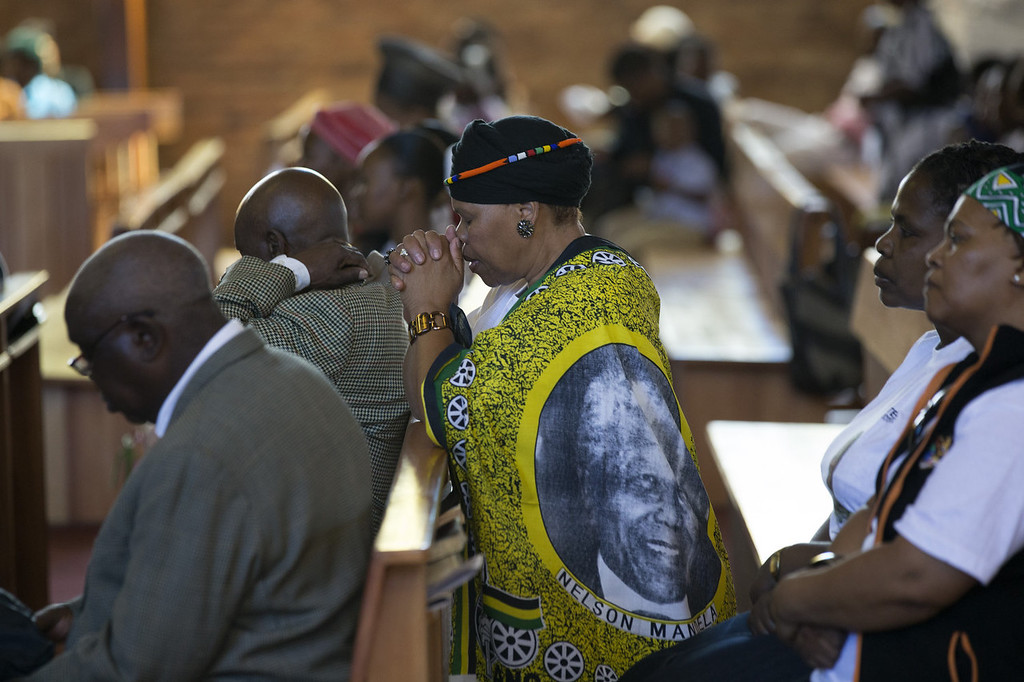 . Members of the congregation pray in Regina Mundi Catholic Church in Soweto Township as the funeral of former South African President takes place in Qunu on December 15, 2013 in Soweto, South Africa. Mr Mandela passed away on the evening of December 5, 2013 at his home in Houghton at the age of 95. Mandela became South Africa\'s first black president in 1994 after spending 27 years in jail for his activism against apartheid in a racially-divided South Africa.  (Photo by Oli Scarff/Getty Images)