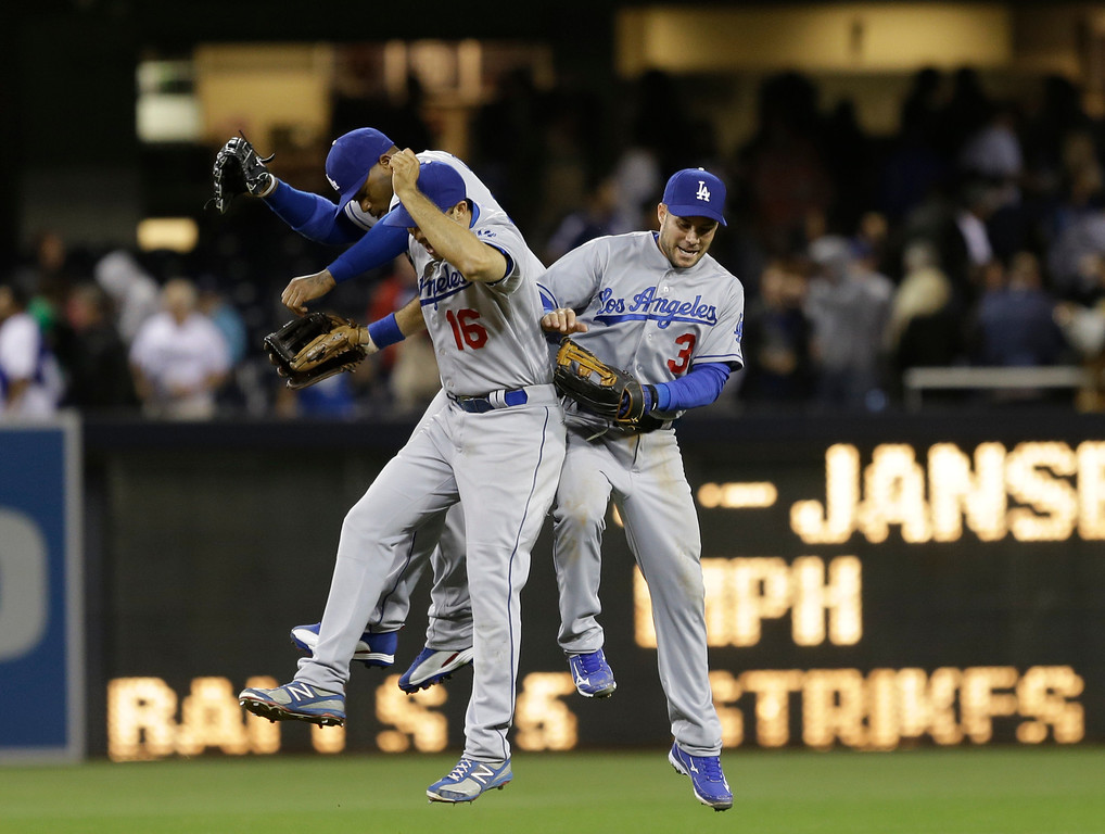 . Los Angeles Dodgers\' Andre Ethier, (front), Skip Schumaker, (right),  and Carl Crawford celebrate after the Dodgers 3-2 victory over the San Diego Padres in baseball game in San Diego, Thursday, April 11, 2013. (AP Photo/Lenny Ignelzi)