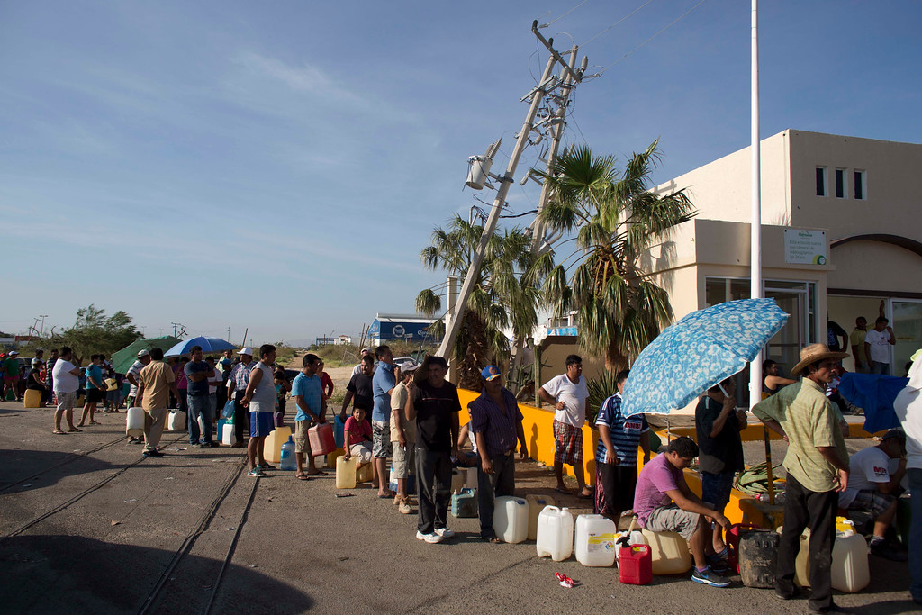 . People wait in line to fill up their jugs and bottles with fuel at a gasoline station in San Jose de los Cabos, Mexico, Thursday, Sept. 18, 2014. After Hurricane Odile roared past, residents of the resort state of Baja California Sur struggled with a lack of power and running water and formed long lines for emergency supplies. The remnants of Odile is now taking aim at the U.S. Southwest. (AP Photo/Dario Lopez-Mills)