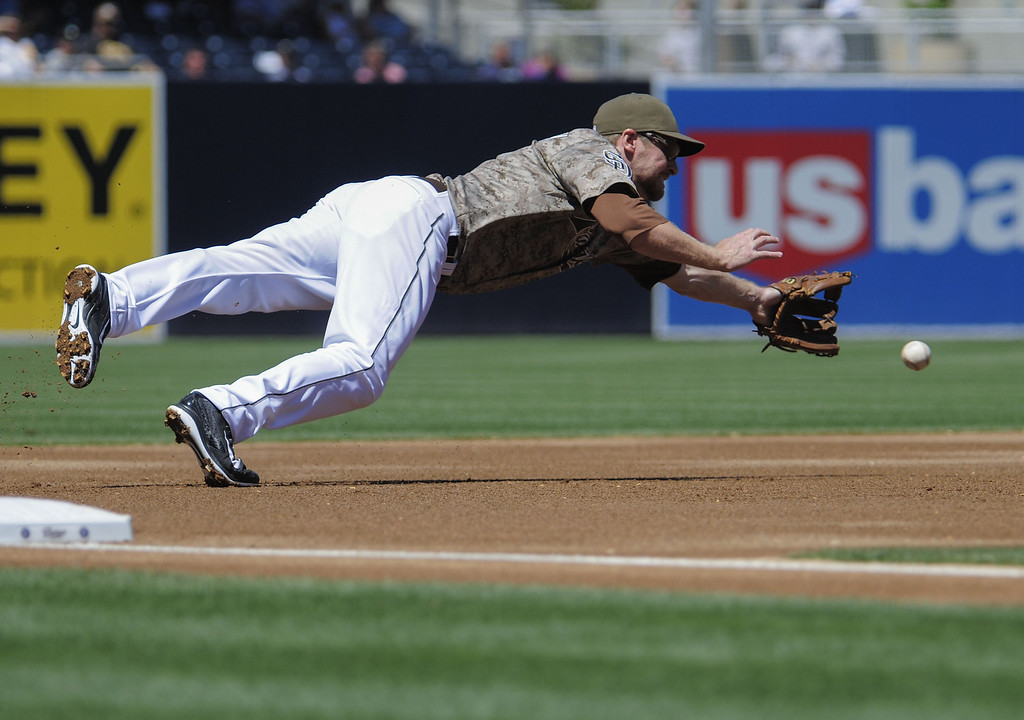. Chase Headley #7 of the San Diego Padres dives but can\'t make the catch on a single hit by Josh Rutledge #14 of the Colorado Rockies during the first inning of a baseball game at Petco Park on September 8, 2013 in San Diego, California.  (Photo by Denis Poroy/Getty Images)