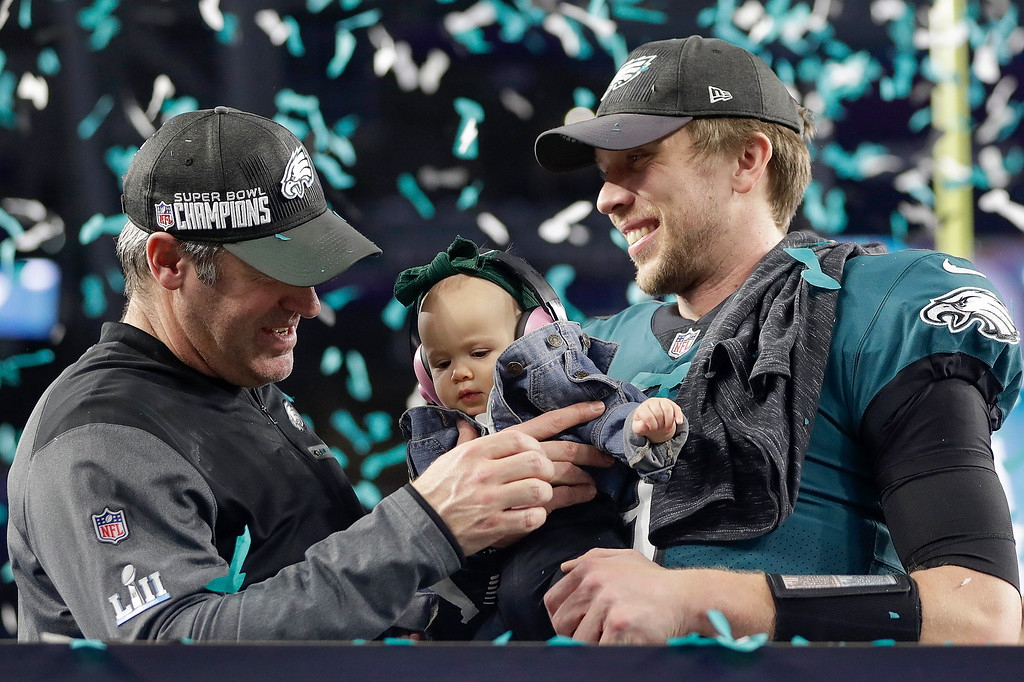 . Philadelphia Eagles\' Nick Foles, right, holds up his daughter, Lily, as he celebrates with head coach Doug Pederson after the NFL Super Bowl 52 football game against the New England Patriots, Sunday, Feb. 4, 2018, in Minneapolis. The Eagles won 41-33. (AP Photo/Mark Humphrey)
