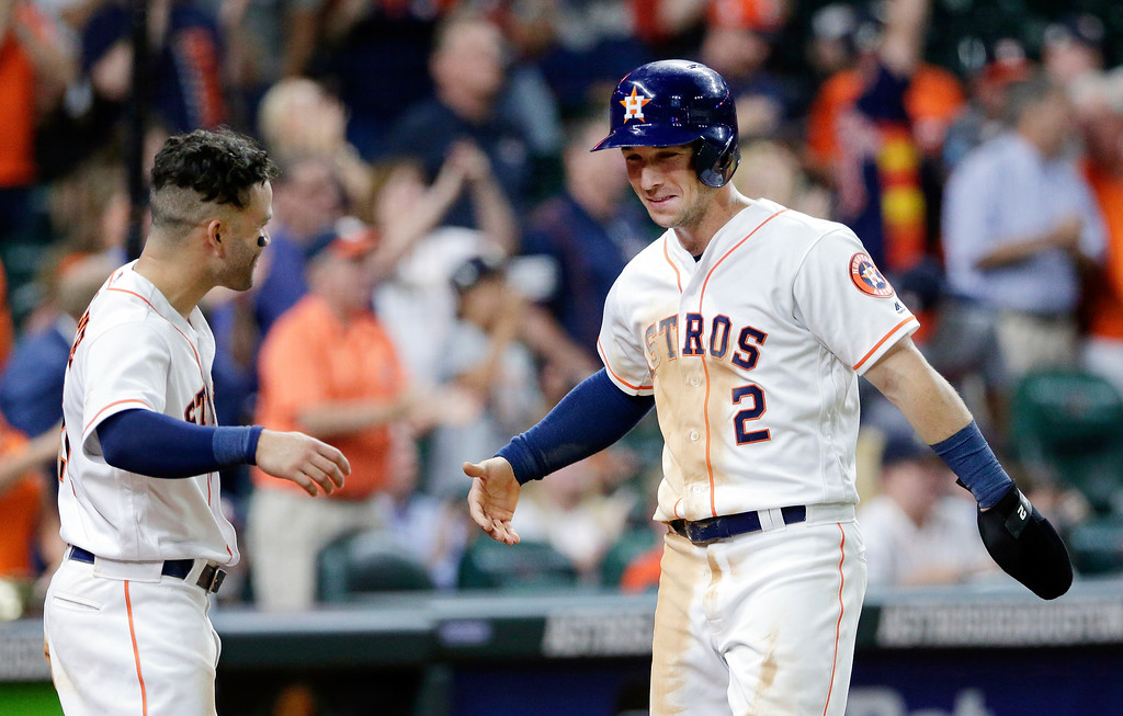 . Houston Astros\' Jose Altuve, left, congratulates Alex Bregman (2) after he scored on a double by Josh Reddick during the eighth inning of a baseball game against the Cleveland Indians, Sunday, May 20, 2018, in Houston. (AP Photo/Michael Wyke)