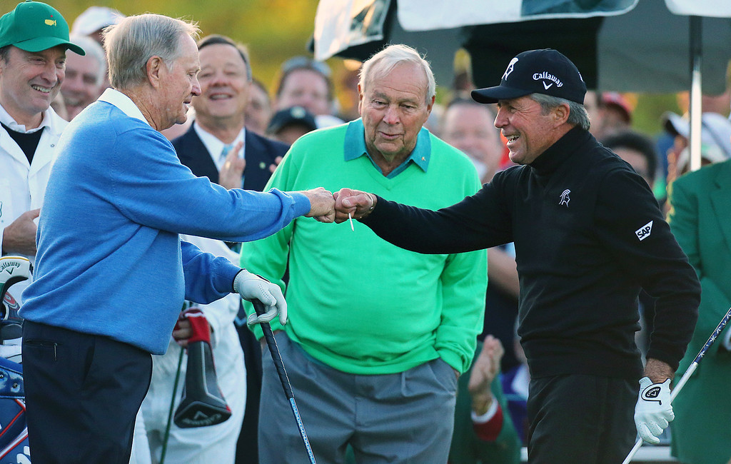 . Arnold Palmer, center, watches as Jack Nicklaus, left, and Gary Player touch fists after Palmer hit his ceremonial drive on the first tee during the first round of the Masters golf tournament Thursday, April 10, 2014, in Augusta, Ga. (AP Photo/Atlanta Journal-Constitution, Curtis Compton)
