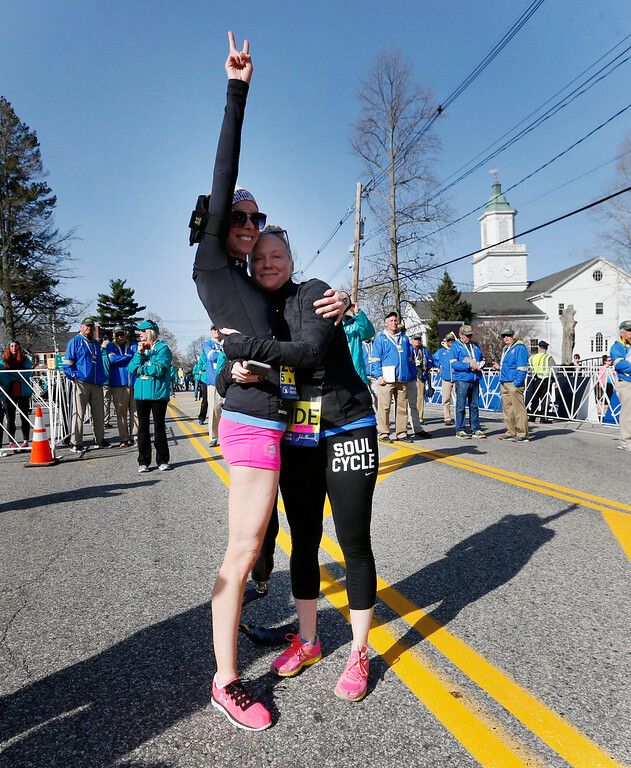 . Boston Marathon bombing survivor Adrianne Haslet, left, gives a victory sign before running the marathon at the start line in Hopkinton, Mass., Monday, April 18, 2016. (AP Photo/Michael Dwyer)