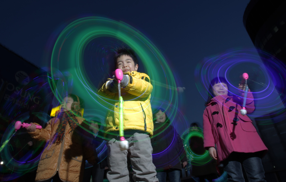 . South Korean children spin illuminated sticks during \'Cyber Jwibulnoli\' at Everland on February 21, 2013 in Seoul, South Korea. Jwibulnoli is originally played on the first full moon of the lunar year, that is February 25 this year.  (Photo by Chung Sung-Jun/Getty Images)