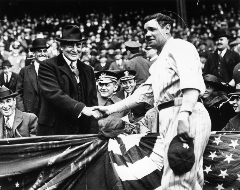 . Great all-round baseball player, Babe Ruth (George Herman Ruth, 1895 - 1948) shakes hands with the 29th President of the USA, Warren Harding. After the handshake Babe Ruth hit a home run to help his team, the New York Yankees win the third game of the series with the Wash.   (Photo by Keystone/Getty Images)