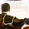 Bullfigher watches as rejoneador Gastón Santos coaxes a bull with his horse.