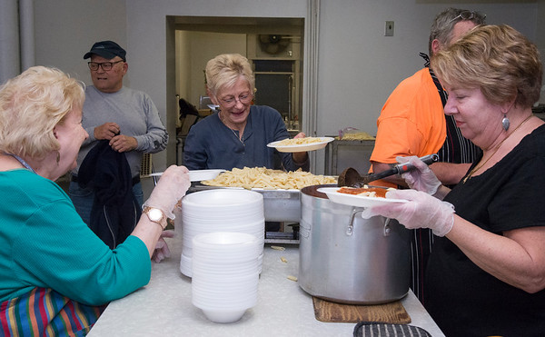 12/05/19 Wesley Bunnell | StaffrrVolunteers at First Lutheran Church in New Britain hold a free pasta dinner every Wednesday night open to all. Barbara Pond, L, Gail Spada and Nancy Michalski put togethers the plates of pasta.