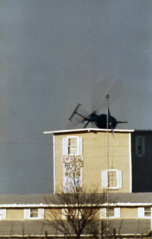 ". A helicopter makes a low pass over the Branch Davidian compound near Waco, Texas on Friday, April 9, 1993. A banner hangs from a window reading: ""1st Seal, Rev 6:12, PS 45, Rev 19, PS 2, PS 18, PS 35, KJV,\"" which refers to several verses from Psalms and Revelation in the Bible. KJV refers to the King James version of the Bible. (AP Photo/David Philip)"