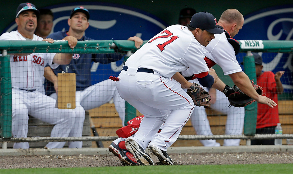 . Boston Red Sox catcher David Ross (3) and third baseman Carlos Rivero (71) collide while chasing a pop foul by Minnesota Twins Josh Willingham during the sixth inning of an exhibition baseball game in Fort Myers, Fla., Saturday, March 29, 2014. (AP Photo/Gerald Herbert)