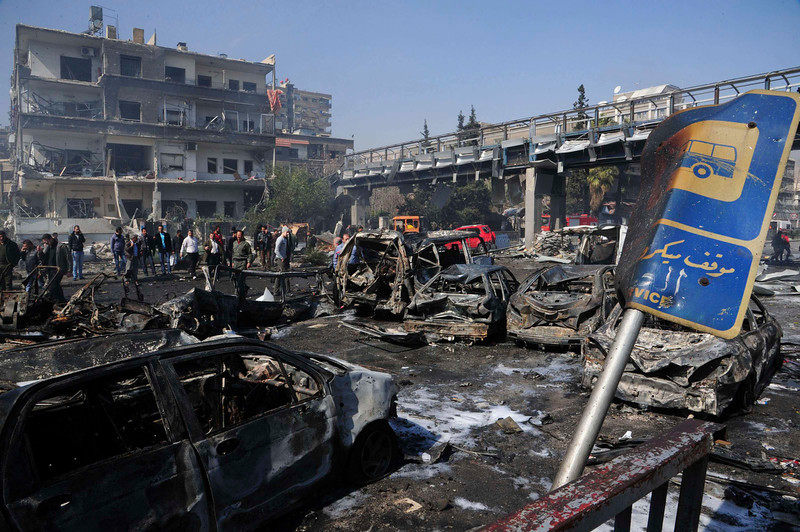 ". People walk near debris and damaged vehicles after an explosion at central Damascus February 21, 2013, in this handout photograph released by Syria\'s national news agency SANA. The big explosion shook the central Damascus district of Mazraa on Thursday, residents said, and Syrian state media blamed what it said was a suicide bombing on ""terrorists\"" battling President Bashar al-Assad. Syrian television broadcast footage of at least four bodies strewn along a main street and firefighters dousing the charred remains of dozens of burning vehicles. Black smoke billowed into the sky. REUTERS/Sana"