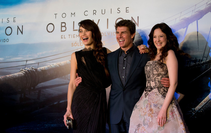 ". U.S. actor Tom Cruise, center, embraces actress Olga Kurylenko, left, and Andrea Riseborough as they posse for pictures during a presentation to promote the film ""Oblivion\"" in Buenos Aires, Argentina,  Tuesday, March 26, 2013. (AP Photo/Natacha Pisarenko)"