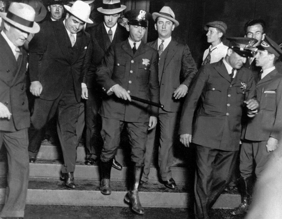 ". Alphonse ""Al\"" Capone, left, in white hat, as he emerged from the Federal Building after trial Dec. 10, 1931 in Chicago.  (AP Photo)"