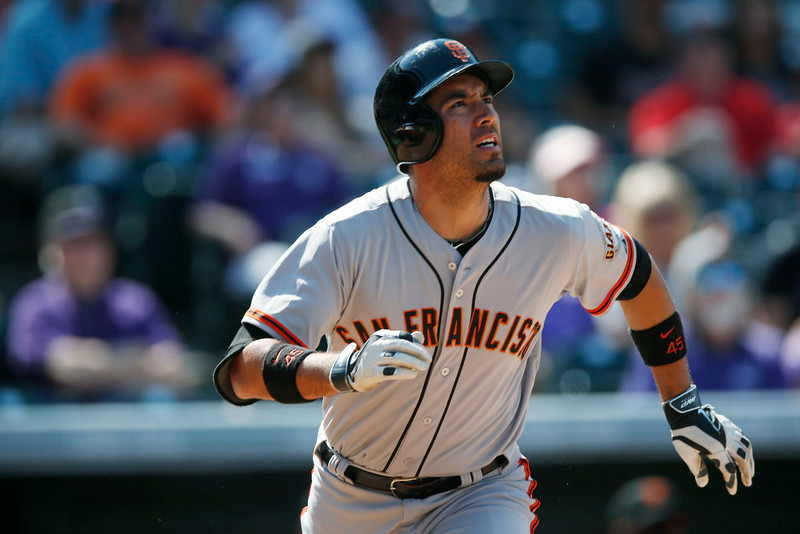. San Francisco Giants pinch-hitter Travis Ishikawa follows the flight of his RBI-single against the Colorado Rockies in the eighth inning of the Giants\' 4-2 victory in a baseball game in Denver on Monday, Sept. 1, 2014. The game was resumed in the bottom of the sixth inning of play when it was suspended because of rain on May 22. (AP Photo/David Zalubowski)