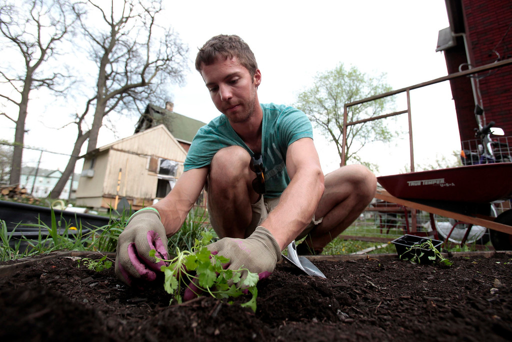 . Darin McLeskey, 22-years-old, plants a vegetable garden in the back yard of one of the properties he purchased at a Wayne County auction and plans on refurbishing in Detroit, Michigan May 9, 2013. Low property prices in Detroit in the wake of the housing crash in 2008 have lured investors from California to China. Speculators bank on high returns despite a financial crisis so dire Detroit\'s state-appointed emergency manager, Kevyn Orr, has cited a 50-50 chance the city will file for bankruptcy. Picture taken May 9, 2013.  REUTERS/ Rebecca Cook