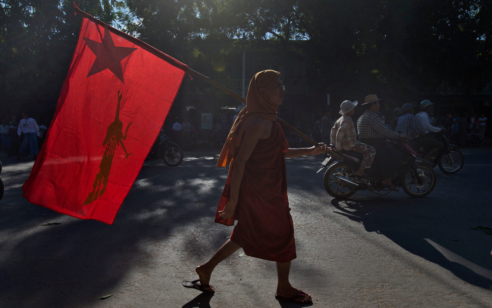 Description of . A Buddhist monk who supports Myanmar opposition leader Aung San Suu Kyi walks with a flag of her National League of Democracy after welcoming her in Monywa town, northwestern Myanmar, Thursday, Nov. 29, 2012. Security forces used water cannons, tear gas and smoke bombs Thursday to clear protesters from a copper mine in northwestern Myanmar, wounding villagers and Buddhist monks just hours before Suu Kyi arrived in the area to hear their grievances. (AP Photo/Gemunu Amarasinghe)