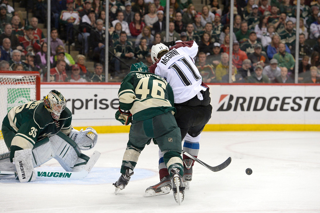 . Minnesota Wild goalie Darcy Kuemper (35) watches the bouncing puck as Colorado Avalanche left wing Jamie McGinn (11) tries to get his stick on it with Minnesota Wild defenseman Jared Spurgeon (46) on defense during the second period  April 24, 2014 in Game 4 of the Stanley Cup Playoffs at Xcel Energy Center. (Photo by John Leyba/The Denver Post)