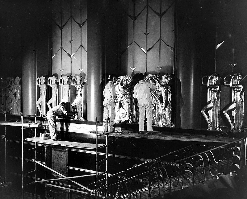 . Painters put the finishing touches on the sculptures in the Paramount Theatre\'s lobby in Oakland in 1973. The four-story lobby features large vertical panels with more than 50 golden statues of ancient Egyptian women. (Bay Area News Group Staff Archives)