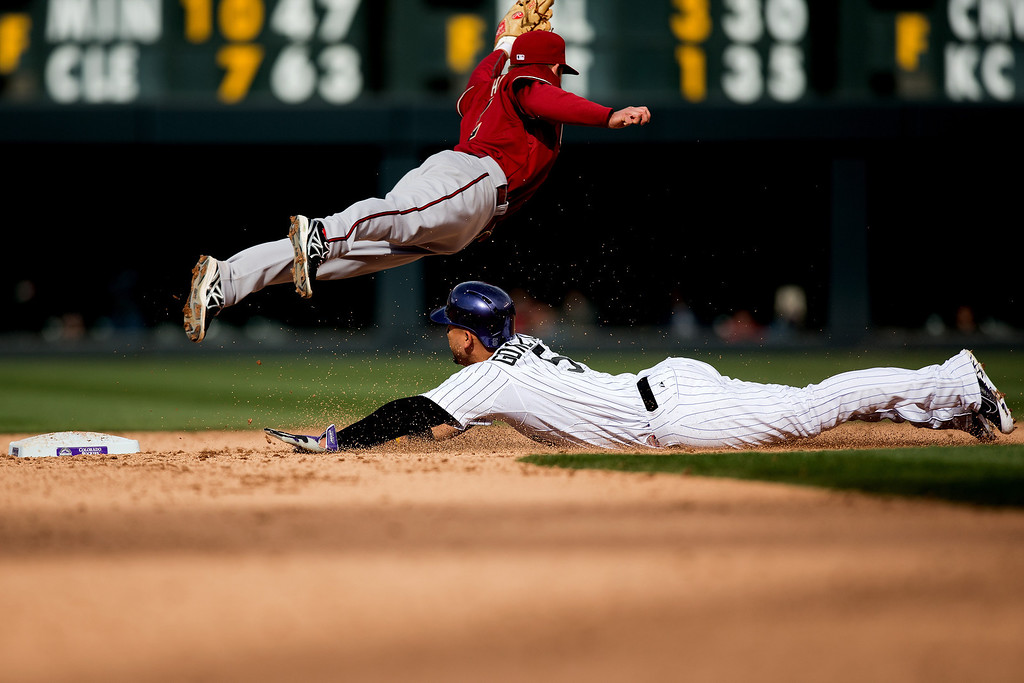 . Carlos Gonzalez #5 of the Colorado Rockies slides in to steal second base as second baseman Aaron Hill #2 of the Arizona Diamondbacks dives for the wild throw from catcher Miguel Montero #26 (not pictured) during the ninth inning at Coors Field on April 6, 2014 in Denver, Colorado. The Diamondbacks defeated the Rockies 5-3. (Photo by Justin Edmonds/Getty Images)