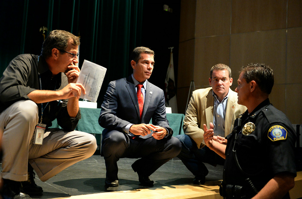 . Murrieta Mayor Alan Long, center, chats with councilman Randon Lane, second from right, and police officer Dennis Vrooman, right, prior to a town hall meeting on Wednesday, July 2, 2014 at Murrieta Mesa High School in Murrieta, Ca. The meeting is being held in response to immigrants who were being processed through a Texas Border Patrol Station and delivered to the Murrieta Border Patrol Station on Tuesday, which created protests from both sides of the immigration issue. (Micah Escamilla/The Sun)
