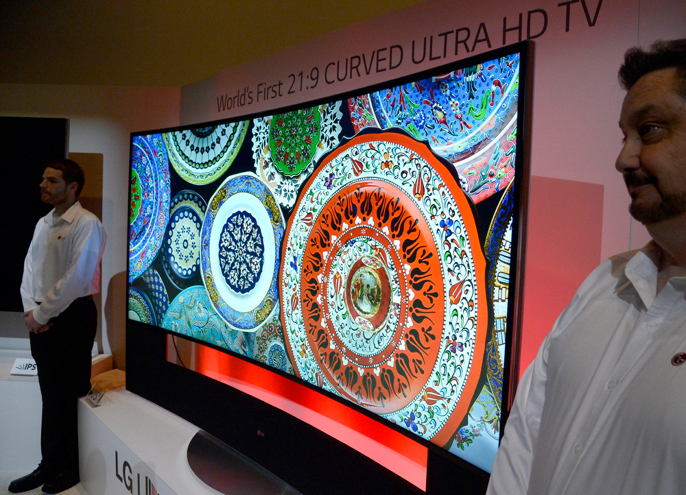 Description of . The world's first curved television the LG Curved Ultra  108 inch HD TV is guarded by LG employees after being unveiled at the press day at the consumer electronics show CES in Las Vegas, USA, 06 January 2014. CES, the world's largest annual consumer technology trade show runs from 07 to 10 January 2014 and is expected to feature 3,200 exhibitors showing off their latest products and services to about 150,000 attendees.  EPA/MICHAEL NELSON