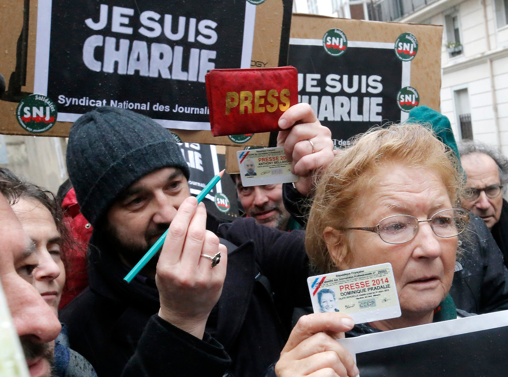. Journalist show their press cards and a pencil during a minute of silence outside the Charlie Hebdo newspaper in Paris, Thursday, Jan. 8, 2015, a day after masked gunmen stormed the offices of a satirical newspaper and killed 12 people. Tensions in Paris were high as France began a day of national mourning. The most senior security official abandoned a top-level meeting after just 10 minutes to rush to a shooting on the city\'s southern edge. A policewoman died and a street sweeper was wounded. The shooter remained at large. (AP Photo/Francois Mori)