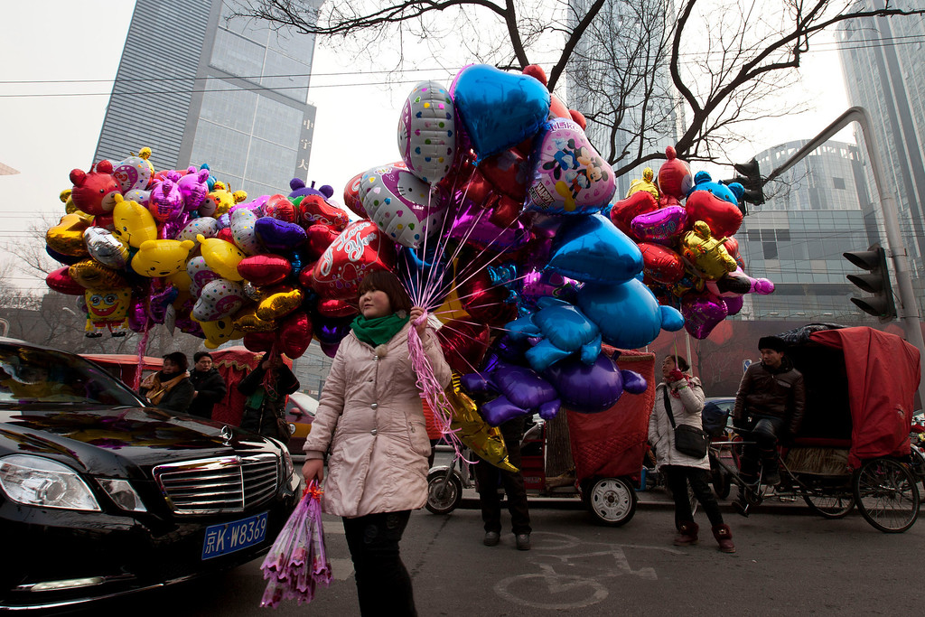 . Vendors hold roses and balloons as they wait for customers near a shopping mall on the Valentines Day in Beijing, China, Friday, Feb. 14, 2014. (AP Photo/Alexander F. Yuan)