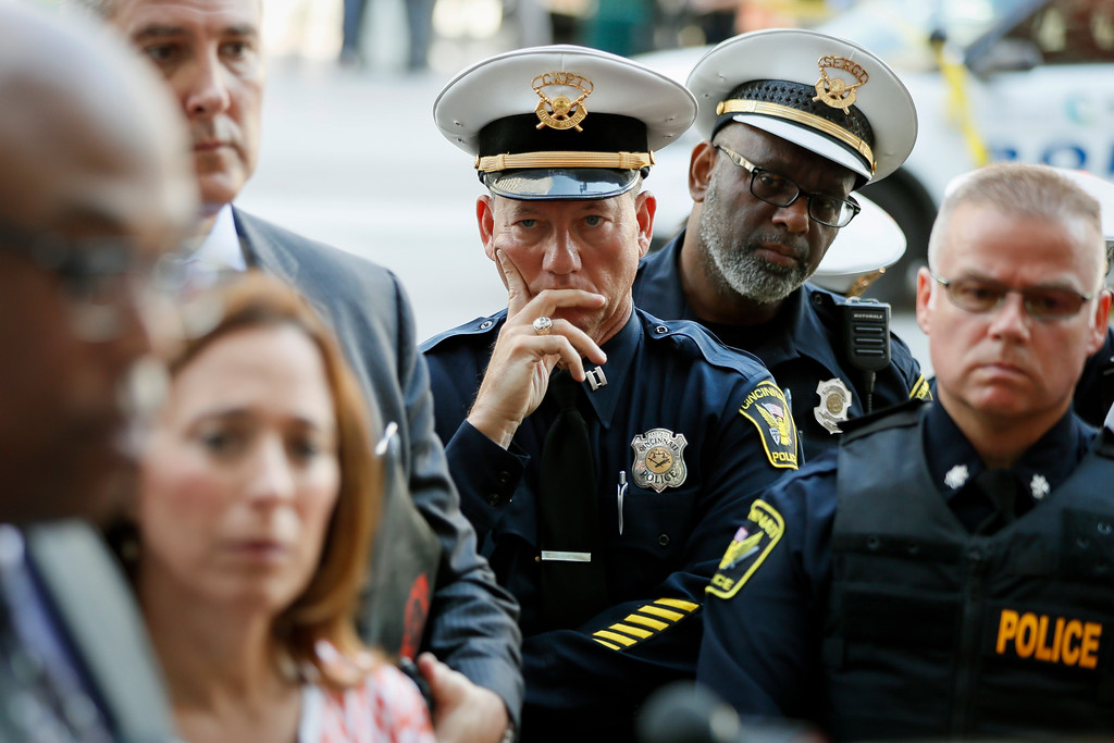 . Members of the Cincinnati Police Department listen as Chief Eliot Isaac speaks to the media as emergency personnel and police work the scene of a shooting near Fountain Square, Thursday, Sept. 6, 2018, in downtown Cincinnati. (AP Photo/John Minchillo)