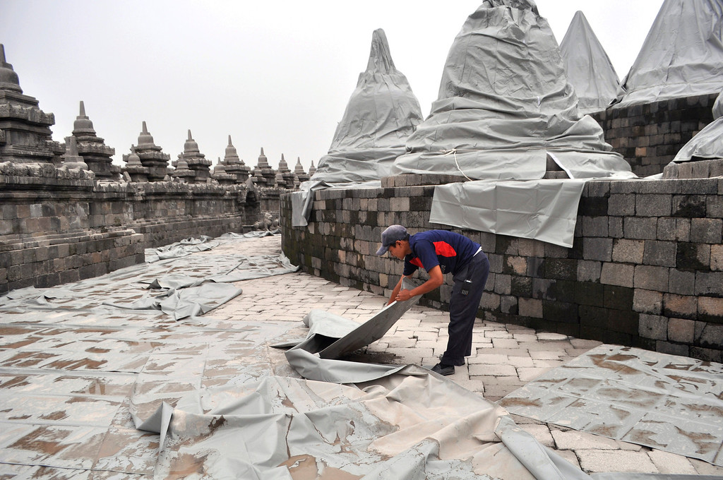 . A worker spreads plastic sheets to cover Borobudur temple to protect from volcanic ash, from an eruption of Mount Kelud, in Magelang, central Java, Indonesia, Friday, Feb. 14, 2014. (AP Photo/Slamet Riyadi)