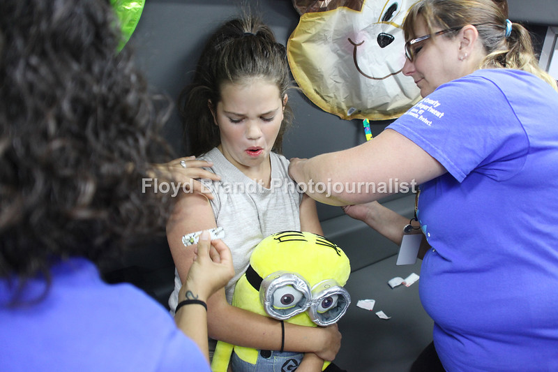Havre Daily News/Floyd Brandt   Willow Riggin gets the shots she needs for school from nurses Jessica Kennedy-Stiffarm (left) who puts on a bandaid to cover the area and Wanda Meredith  at Lil' Shots Carnival Friday. She received two shots one in each arm both at the same time