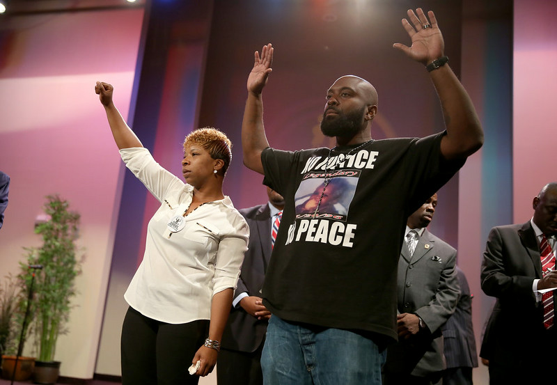 . Lesley McSpadden (L) and Michael Brown, the parents of slain 18-year-old Michael Brown, acknowledge a crowd during an event at the Greater Grace Church on August 17, 2014 in Ferguson, Missouri. The event was lead by the Rev. Al Sharpton in support of justice for Michael Brown who was killed by police on August 9th. (Photo by Joe Raedle/Getty Images)