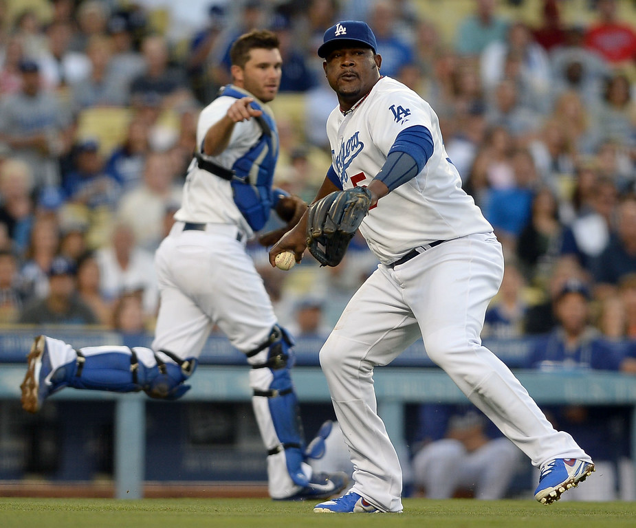 . Los Angeles Dodgers Juan Uribe prepares to throw out a Cleveland Indians batter after fielding a bunt July 1, 2014 in Los Angeles.(Andy Holzman/Los Angeles Daily News)