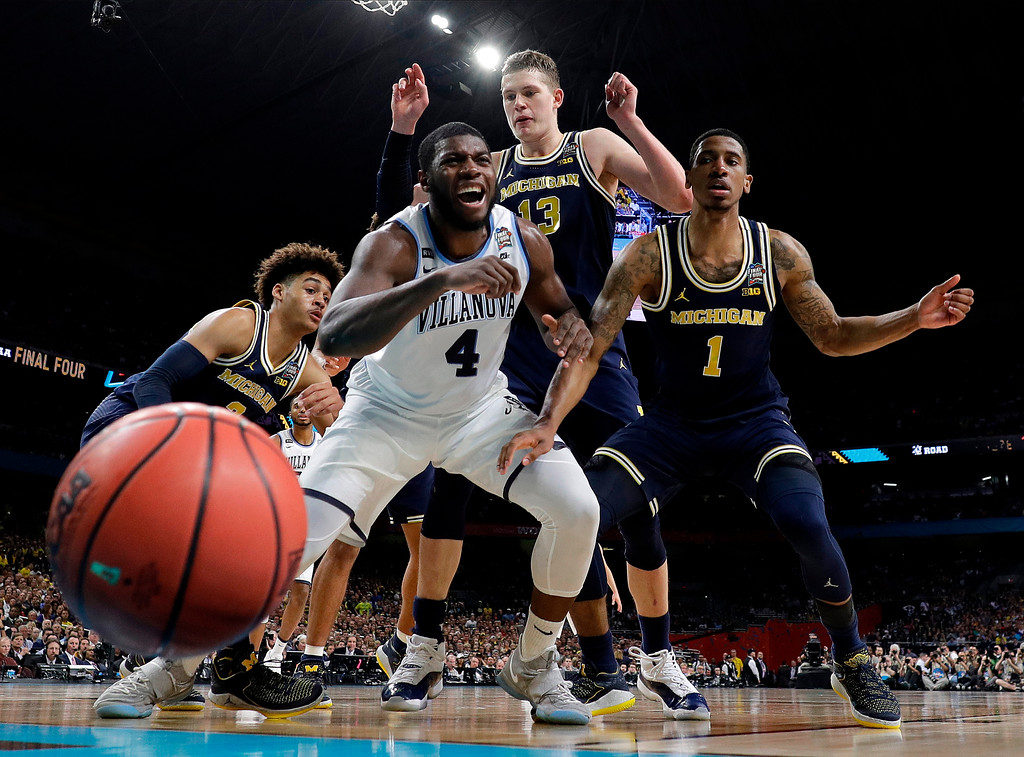 . Villanova\'s Eric Paschall (4) reacts as he loses the control of the ball against Michigan\'s Moritz Wagner (13) and Charles Matthews (1) during the first half in the championship game of the Final Four NCAA college basketball tournament, Monday, April 2, 2018, in San Antonio. (AP Photo/Eric Gay)