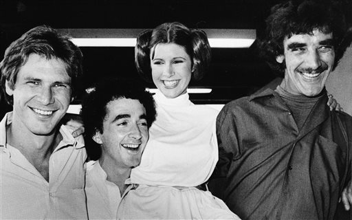 """. FILE - In this Oct. 5, 1978 file photo, actors featured in the \""""Star Wars\"""" movie, from left, Harrison Ford who played Han Solo, Anthony Daniels who played the robot C3P0, Carrie Fisher who played the princess, and Peter Mayhew who played the Wookie, Chewbacca, are shown during a break from the filming of a television special presentation in Los Angeles. Mayhew has had double knee-replacement surgery at a Texas hospital.  (AP Photo, File)"""