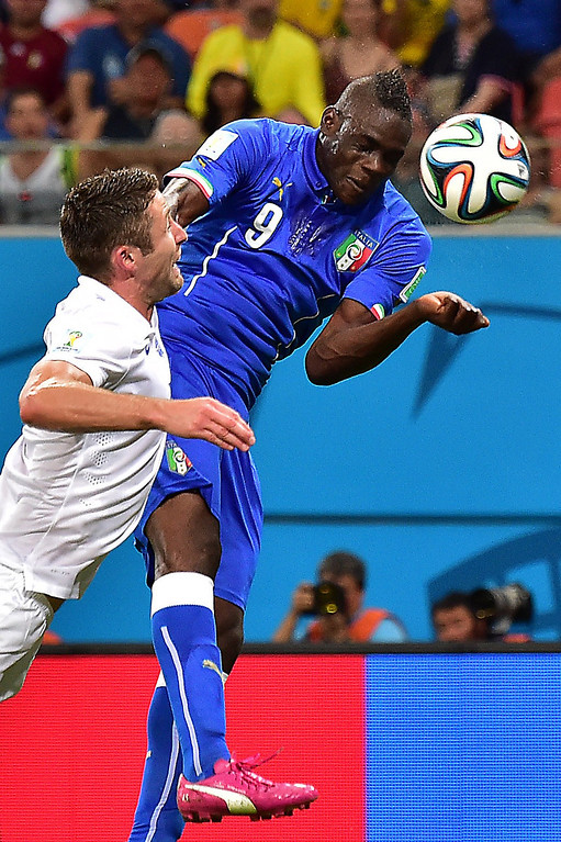 . Italy\'s forward Mario Balotelli (R) heads the ball to score a goal as England\'s defender Gary Cahill defends during a Group D football match between England and Italy at the Amazonia Arena in Manaus during the 2014 FIFA World Cup on June 14, 2014.  AFP PHOTO / GIUSEPPE CACACE