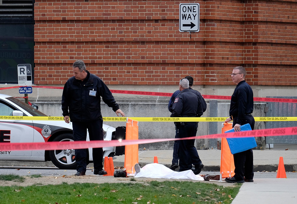 . Police cover the body of a suspect outside Watts Hall on the campus of Ohio State University in Columbus, Ohio, following an attack on campus that left several people injured on Monday, Nov. 28, 2016. The man, identified as Abdul Razak Ali Artan, plowed his car into a group of pedestrians and began stabbing people with a butcher knife Monday before he was shot to death by a police officer.  (Adam Cairns/The Columbus Dispatch via AP)